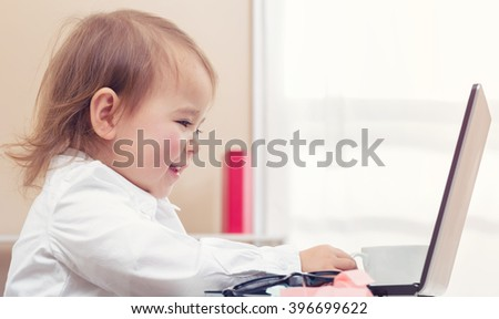 Happy toddler girl working on her laptop - stock photo
