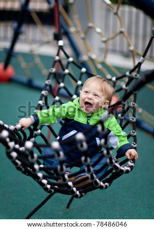Happy toddler in a hammock at a playground - stock photo
