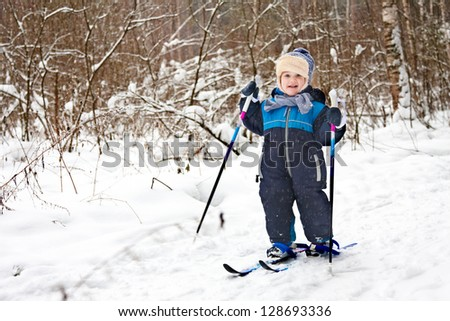 Happy toddler is skiing in winter forest - stock photo