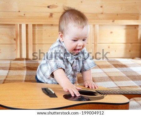 Happy toddler playing guitar - stock photo