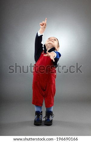 Happy toddler pointing up, over gray background - stock photo