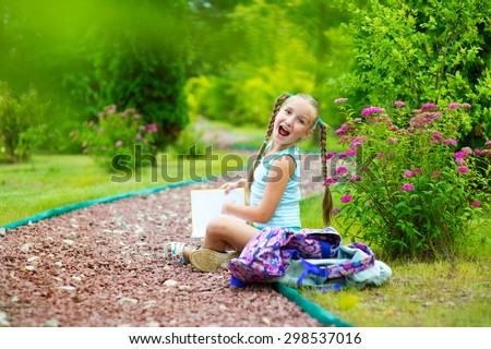 Happy toddler school girl in blue suit sitting on road in summer garden with flowers and reading book with smile - stock photo