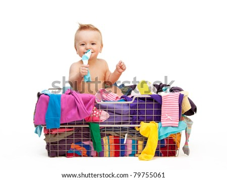 Happy toddler sitting  in basket with clothes - stock photo