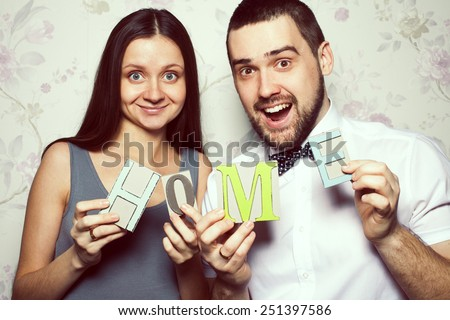 Happy together concept. Portrait of funny hipsters in stylish clothing posing together with letters making HOME word. Vintage style. Close up. Studio shot - stock photo