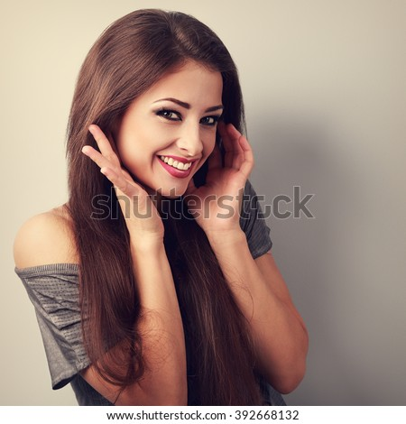 Happy toothy laughing brunette young woman with hands near face. Toned closeup portrait - stock photo