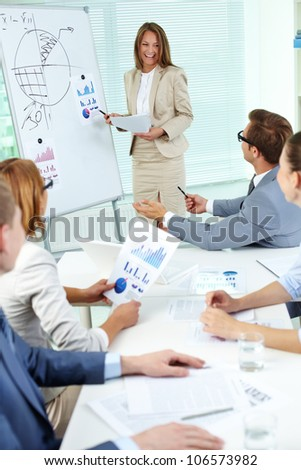 Happy top manager standing by the whiteboard and interacting with business partners at seminar - stock photo