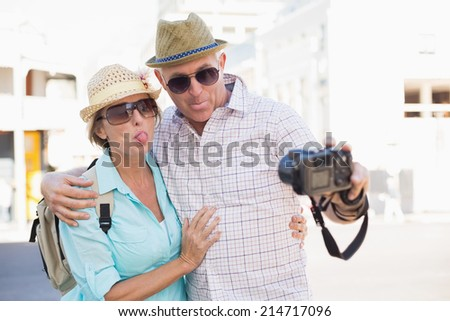 Happy tourist couple taking a selfie in the city on a sunny day - stock photo