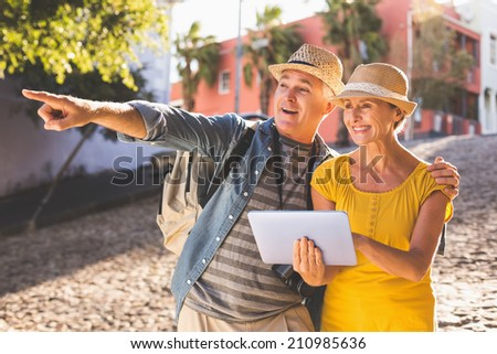 Happy tourist couple using tablet pc in the city on a sunny day - stock photo
