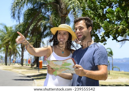 Happy tourist couple with map pointing at destination - stock photo