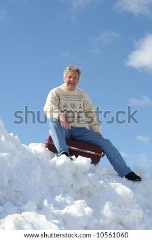 Happy tourist sitting on a suitcase - stock photo