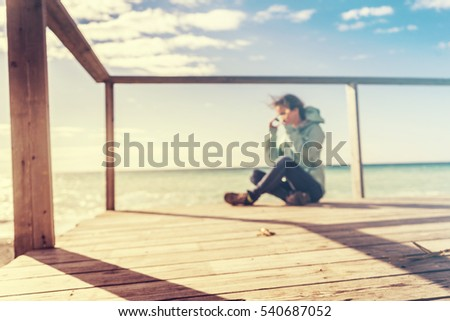 Happy tourist  teenager /student/hipster sitting on wooden railing bench at sunny shore near water, summer travel concept, space for text,sand bitch.Woman smiling and looking away