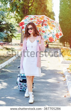 Happy tourist woman in sunglasses and umbrella with suitcase - stock photo