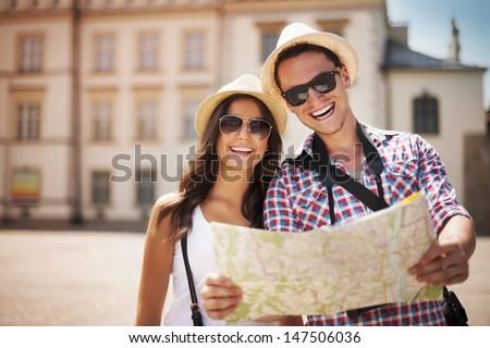 Happy tourists couple holding map  - stock photo