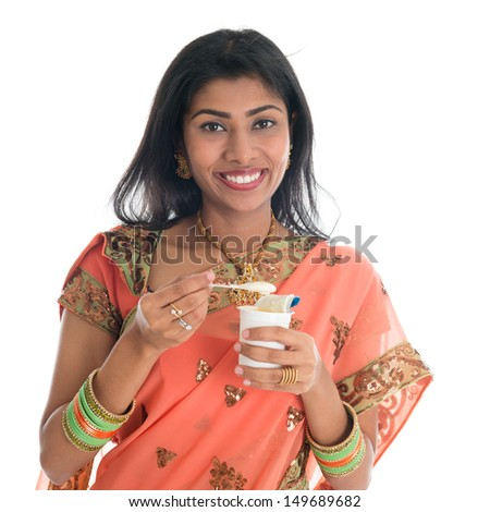 Happy Traditional Indian woman in sari eating yogurt, isolated on white background.