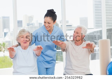 Happy trainer assisting senior couple to exercise in gym - stock photo