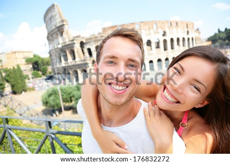 Happy travel couple in piggyback by Coliseum, Rome, Italy. Smiling young romantic couple in love traveling in Europe having fun together in front of Colosseum. Caucasian Man and Asian woman portrait - stock photo