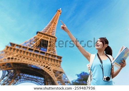 Happy travel woman in Paris with Eiffel Tower and she pointing building, asian beauty - stock photo