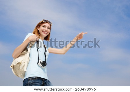 Happy travel woman smile to you and show something by finger with sky background, caucasian beauty - stock photo