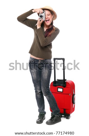 Happy traveler with camera and suitcase going on vacation. - stock photo