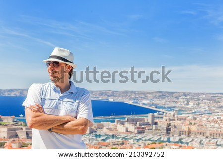 Happy traveling! Handsome man in a hat and sunglasses posing against the city of Marseille - stock photo