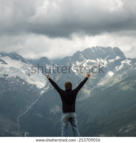 happy traveller on the top of mountain stormy landscape - stock photo