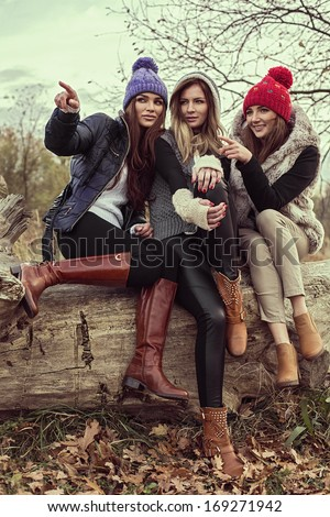 Happy tree girls wearing a woolly hats and showing something  - stock photo