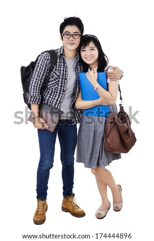 Happy trendy college students with bags and books, posing together, smiling at camera, - stock photo