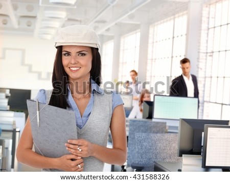 Happy trendy female office worker at busy workplace. - stock photo