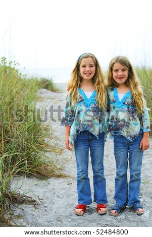 happy twin sisters on the beach vertical - stock photo
