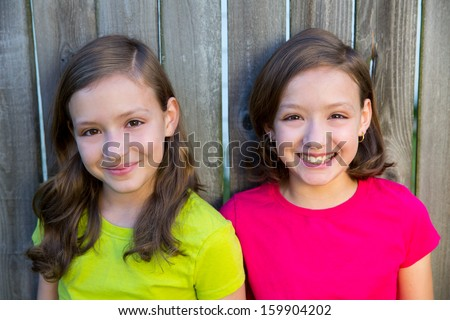Happy twin sisters with different hairstyle smiling on wood backyard fence - stock photo