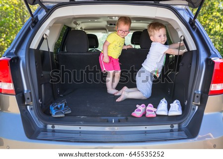 Happy twins playing in the car trunk