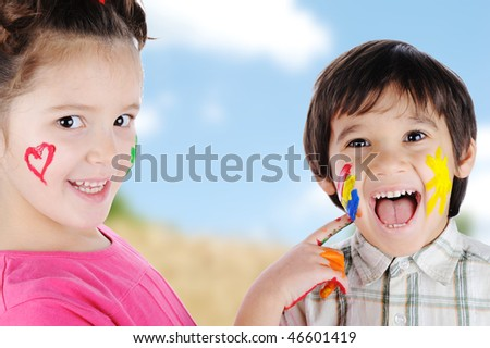 Happy two children outdoor, playing with colors - stock photo