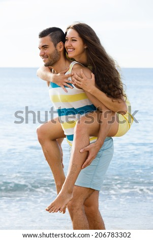 Happy two having date on sandy beach at sunny day - stock photo
