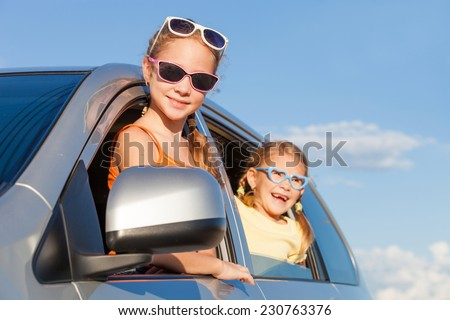 Happy two sisters are sitting in the car at the day time - stock photo