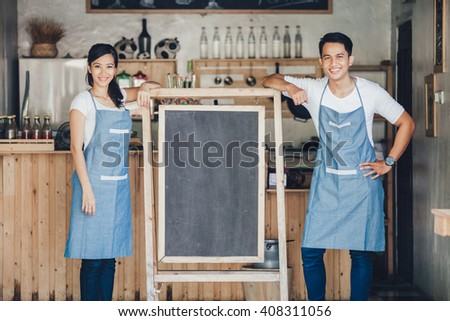happy two small business owner ready to open their cafe. standing with blank board