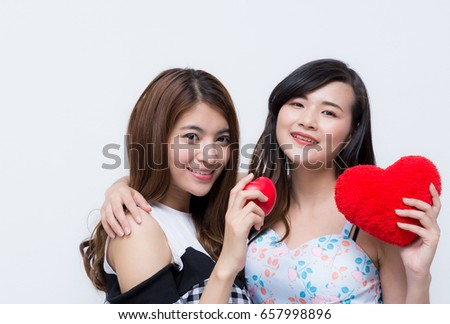 Happy two teenager women holding heart shaped pillow. Valentines day gift ideas,Woman friends showing heart Love and valentines day concept with joyful on white background.