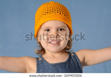 Happy two years girl in yellow knitted cap stands on blue background in studio and looking at camera. She is smiling with open mouth and spread out her arms. - stock photo