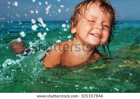 Happy two years old kid swimming and splashing in the sea water - stock photo