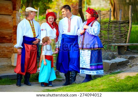 happy ukrainian family in traditional costumes on their homestead - stock photo