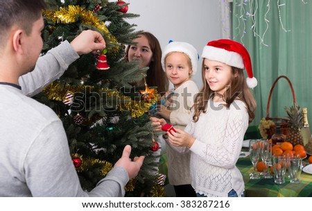 Happy united family of four decorating Christmas tree together at home. Focus on girl - stock photo