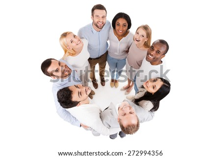 Happy united team. Top view of positive diverse group of happy people in smart casual wear bonding to each other and standing in circle  - stock photo