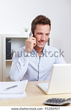 Happy university student making cell phone call at desk - stock photo