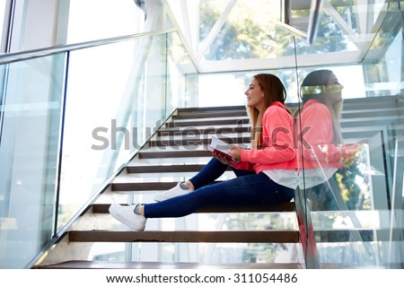 Happy university student reading book while sitting on the steps in interior campus hallway, caucasian teenager girl preparing for lessons at college, copy space area for your text message or content - stock photo