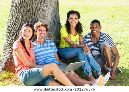 Happy university students with laptop sitting together on college campus - stock photo