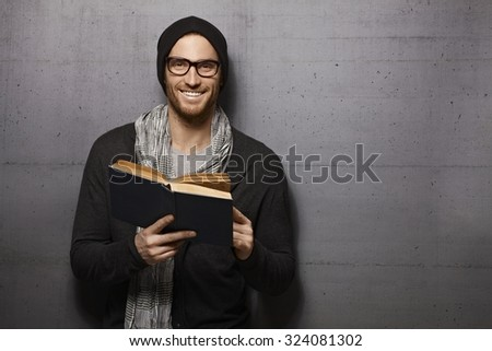 Happy urban style young man standing against grey wall, smiling, reading book, looking at camera. - stock photo