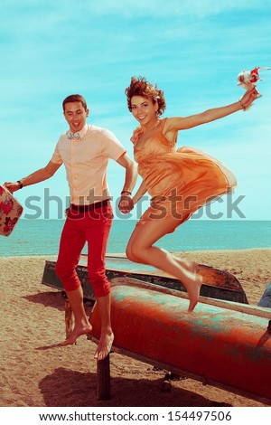 Happy vacation concept. Portrait of a beautiful happy couple of hipsters in trendy clothing jumping at the seaside. Wedding day. Close up. Outdoor shot
