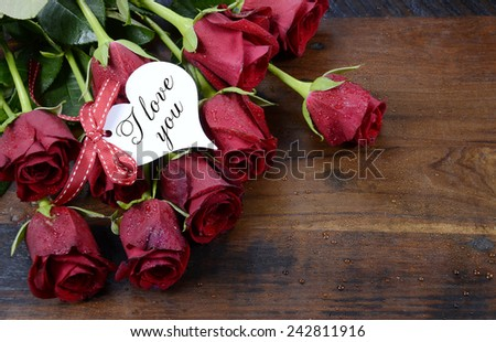 Happy Valentine's Day red roses on dark recycled wood background with I Love You greeting on heart shape gift tag.. - stock photo