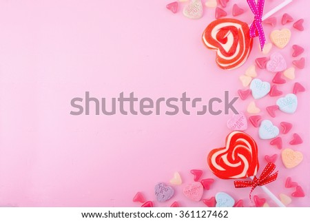 Happy Valentines Day Background with candy and red heart shape lollipops on pink wood background. - stock photo