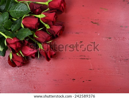Happy Valentines Day background with red roses on distressed vintage recycled wood table. - stock photo