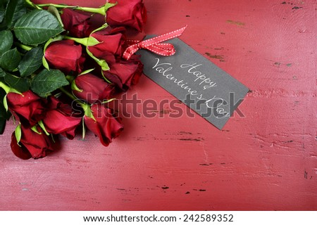 Happy Valentines Day background with red roses with greeting card on distressed vintage recycled wood table. - stock photo